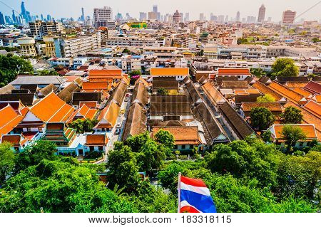 Aerial view of Bangkok monastery and modern office buildings, condominium in Bangkok city downtown with sunset sky, Bangkok , Thailand