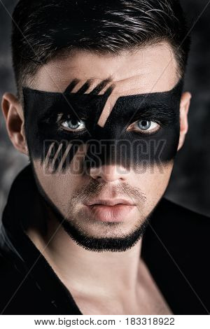 fantasy art  makeup. Young man with black painted mask on face on the dark background. Close up Portrait.  Professional Fashion Makeup.