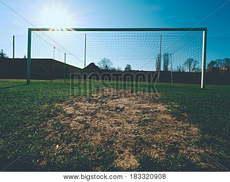 Soccer Football Net Background Over Green Grass And Blurry Stadium.