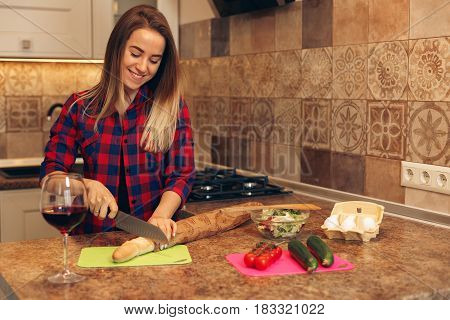 Young woman cooking in the kitchen. Healthy food and vegetable salad. Cooking at home and prepare food.