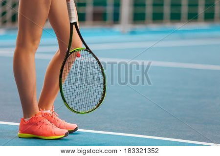 The legs of young girl in a closed tennis court with racket