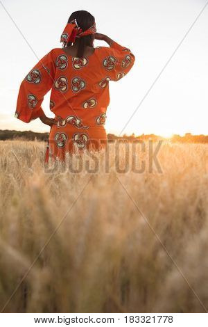 African woman in traditional clothes standing looking across field of barley or wheat crops at sunset or sunrise