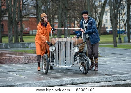RIGA LATVIA - APRIL 22 2017: Tweed ride 2017. Unknown people on the stairs pushing a unique home-made bicycle mobile.