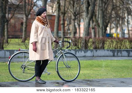 RIGA LATVIA - APRIL 22 2017: Tweed ride 2017. Unknown woman in ancient dress standing at the bike.
