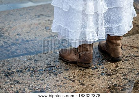 Woman in white dress and winter boots on wet footpaths. Visible only female legs.