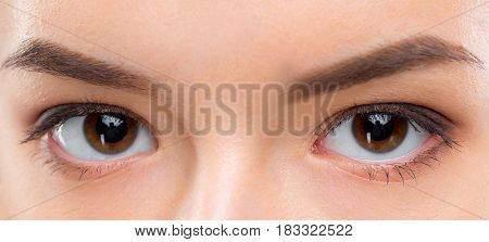 Close up image of two female brown eyes