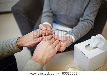Psychiatrist giving helping hand to unhappy patient