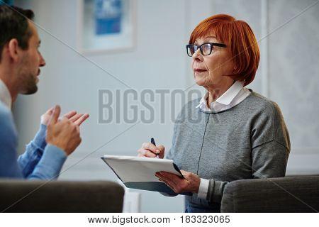 Mature psychologist listening to man story