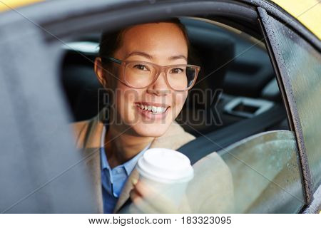 Businesswoman with glass of coffee sitting in cab