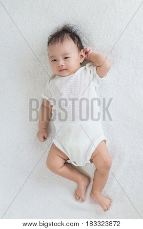 cute Asian baby lying down on bed and scratching head