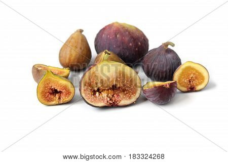 Several varieties of common fig fruits cut open showing the flesh on white background.