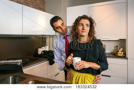 Young businessman embracing to offended curly woman while holding cup of coffee in the kitchen