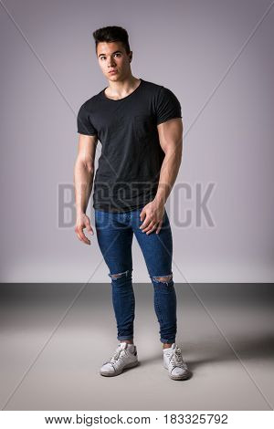 Handsome young muscular man looking at camera in studio shot over neutral background. full length body shot