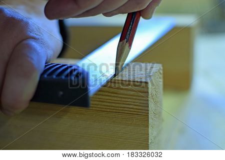 Carpenter marking cutting line to wooden plank.