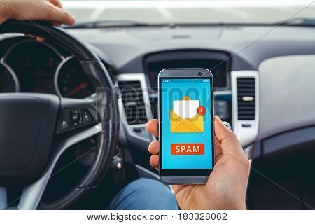 Young man driving a car with a phone in his hand.