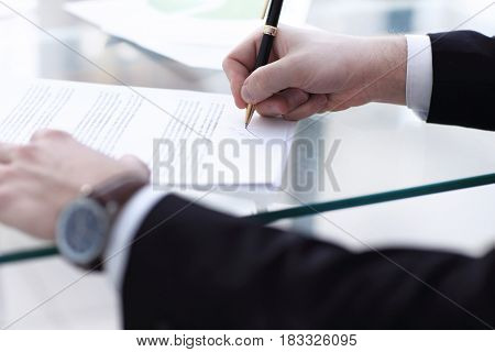 Business man signing a contract in modern light office