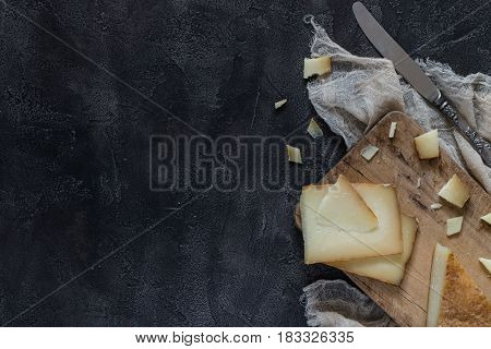 Italian Hard Cheese Pecorino Toscano Sliced And Chopped On Wooden Board With Knife On Dark Rustic Ba