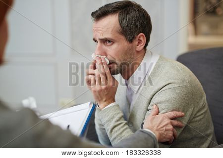Man addicted to alcohol wiping tears during conversation with psychologist
