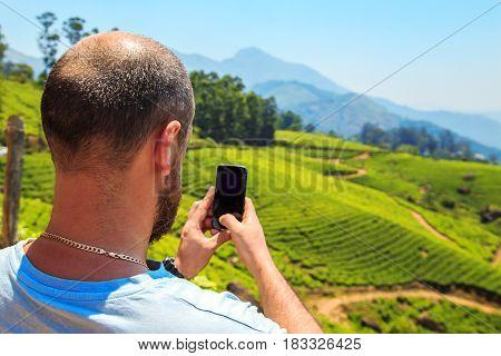 Man inspects the mountain landscape. Munnar Kerala state India. Munnar Kerala state India.