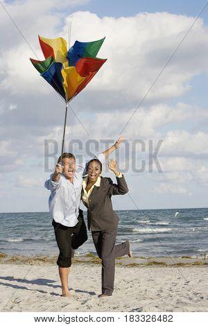 Hispanic businesspeople holding broken beach umbrella