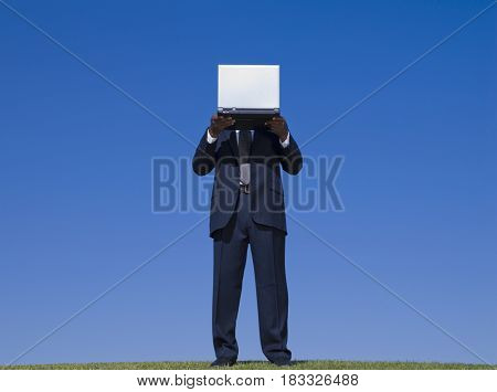 African businessman holding laptop in front of face
