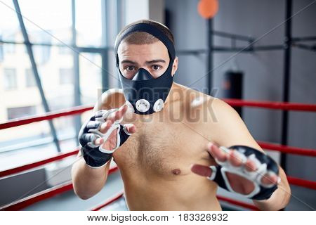 Portrait of shirtless boxer looking at camera while fighting in  ring wearing training mask
