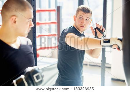 Portrait of young muscular sports man hitting punching bag during boxing practice in fight club, showing to his partner correct speed hitting technique