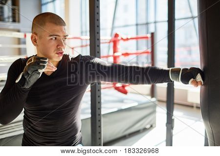 Side view portrait of young muscular sports man hitting punching bag during boxing practice in fight club, training speed and strength
