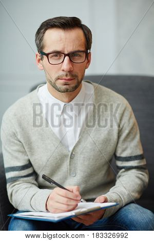Male psychiatrist looking at camera while making notes
