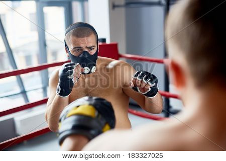 Portrait of young boxer wearing endurance training mask fighting with opponent in boxing ring at fight practice