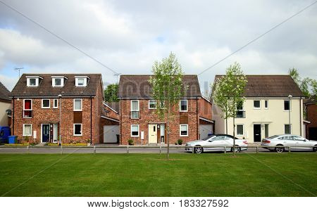 Bracknell, England - April 12, 2017:  Front view of detached houses in a row with cars outside and a green space in front on a modern housing estate in Bracknell, England.