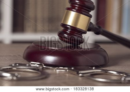 Close up of a judge gavel handcuffs and law books in the background of a courtroom. Selective focus