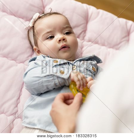 Young mother holding a rattle and playing with her baby girl. Focus on the baby