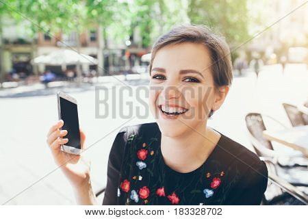 Girl with short pixie haircut is having a phone conversation. People and technology concept. Happy and cheerful expression.