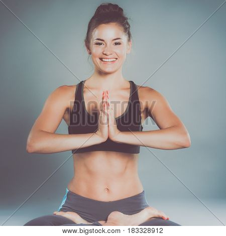 Young woman sitting on the floor in lotus position.