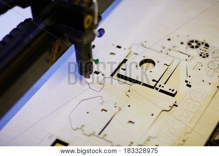 Laser cutter engraving details from veneer wood