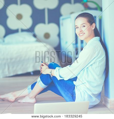Young woman sitting on the floor near childrens cot.