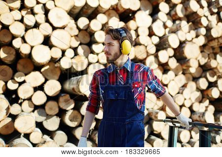 Tree felling worker with headphones pulling cart
