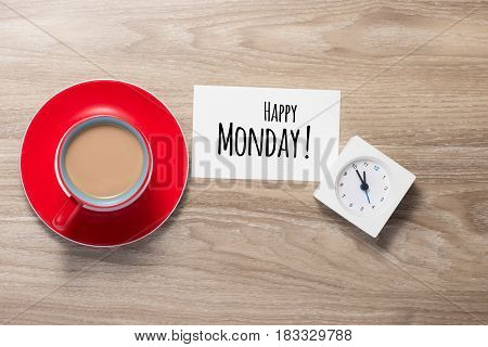 Happy Monday coffee cup on wooden background.