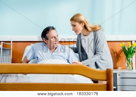 Woman Helping Husband Stand Up From Hospital Bed