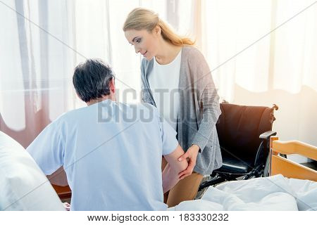 Mature Man Sitting On Hospital Bed With Wife Near By