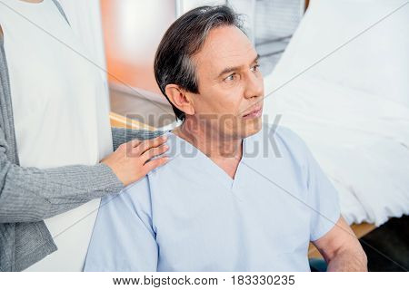 Pensive Wheelchair Man With Wife Near By In Hospital Chamber