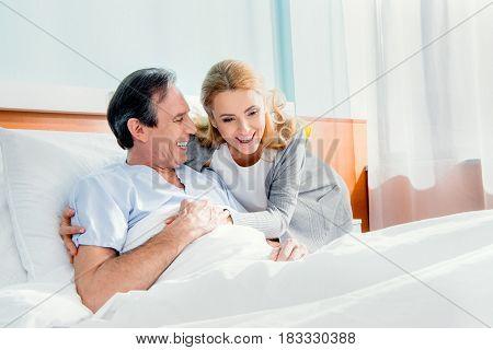 Happy Wife Visiting Elderly Husband In Hospital