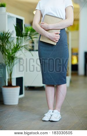 Low section shot below neck of young woman wearing pencil skirt and canvas shoes in office, holding business supplies