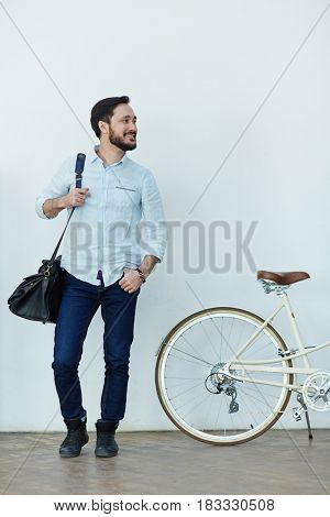Portrait of contemporary  bearded Asian man looking away and smiling happily  while standing against wall with bike dressed in casual clothes