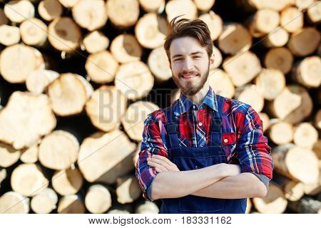 Young lumber standing against pile of firewood