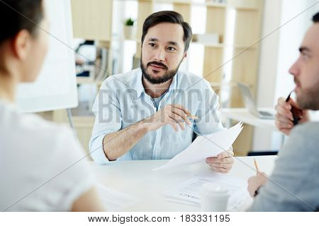 Portrait of bearded Asian man listening intently while discussing business with colleagues during meeting in modern office