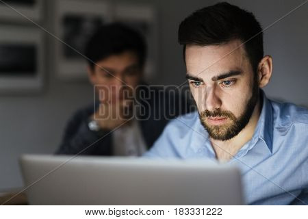 Serious banker looking at online data in laptop