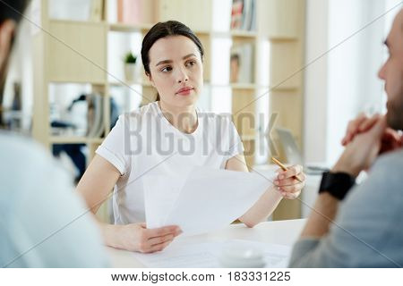 Portrait of young woman listening intently while discussing business with two men during meeting in modern office