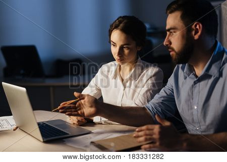 Pretty businesswoman looking at laptop display and listening to co-worker presentation